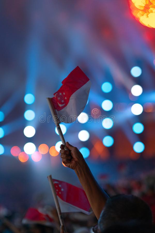 Den 9 augusti 2019 viftade Hand med singapore-flagga under Singapores 54:e nationaldag-parad royaltyfria bilder