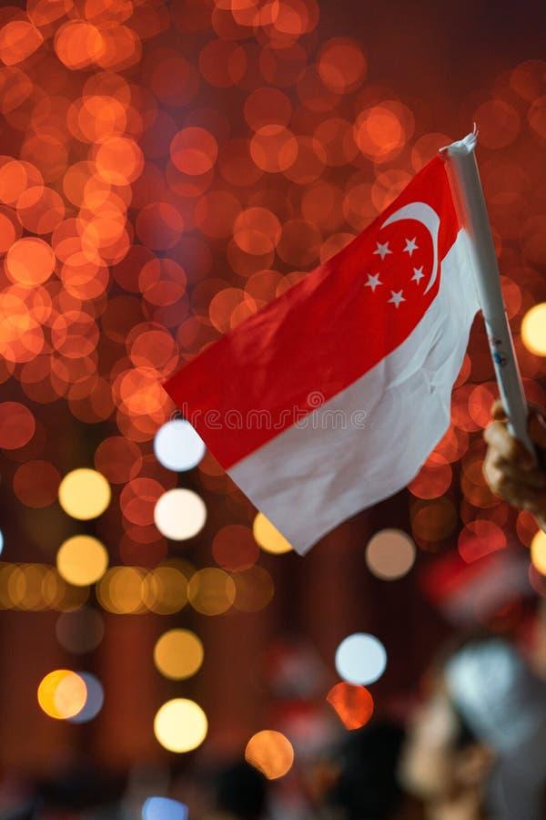 Den 9 augusti 2019 viftade Hand med singapore-flagga under Singapores 54:e nationaldag-parad arkivfoto