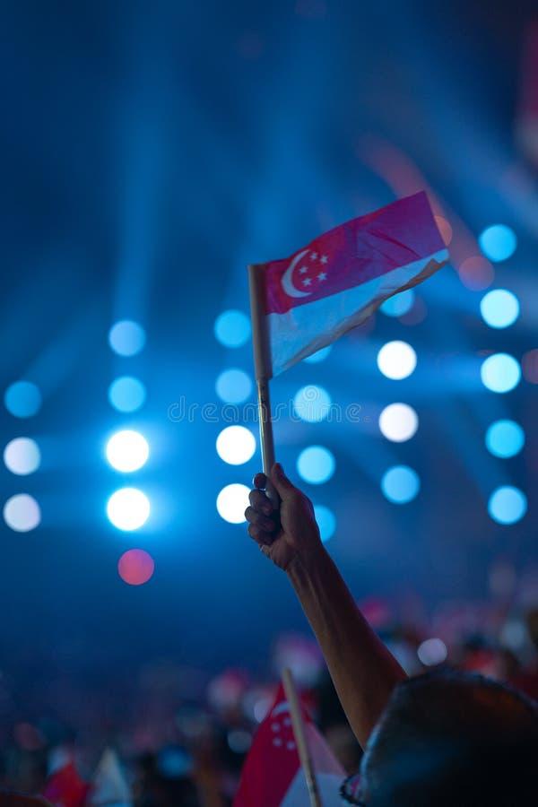 Den 9 augusti 2019 viftade Hand med singapore-flagga under Singapores 54:e nationaldag-parad royaltyfri bild