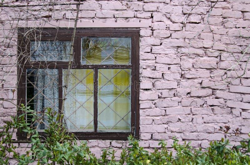 Den autentiska fönsterramen av en lantlig stuga med den rosa tegelstenväggen och blomkrukor monterade den grungy väggen royaltyfria foton