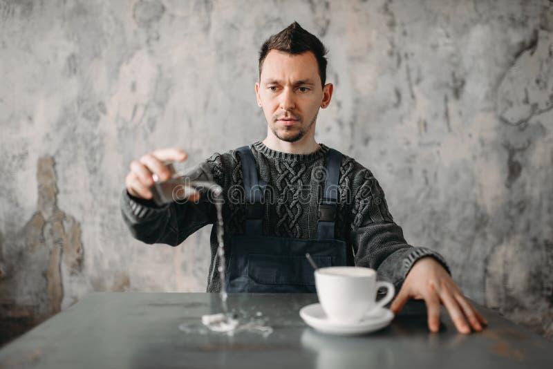 Den autistiska mannen häller vatten från exponeringsglaset på tabellen royaltyfri fotografi