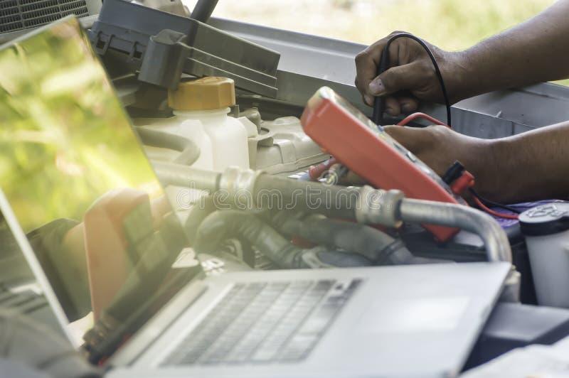 Den auto mekanikern använder en multimetervoltmeter fotografering för bildbyråer
