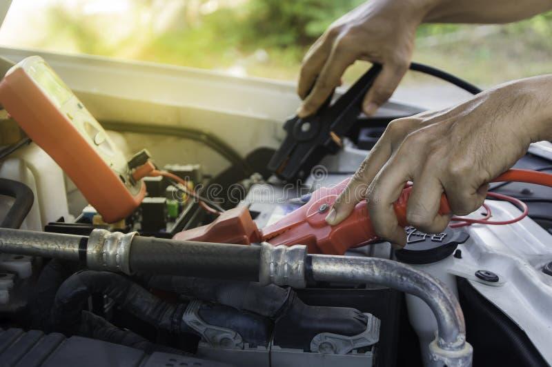 Den auto mekanikern använder ett laddande batteri med elektricitetshoju arkivfoton