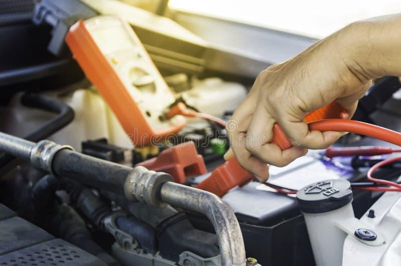 Den auto mekanikern använder ett laddande batteri med elektricitetshoju arkivbilder