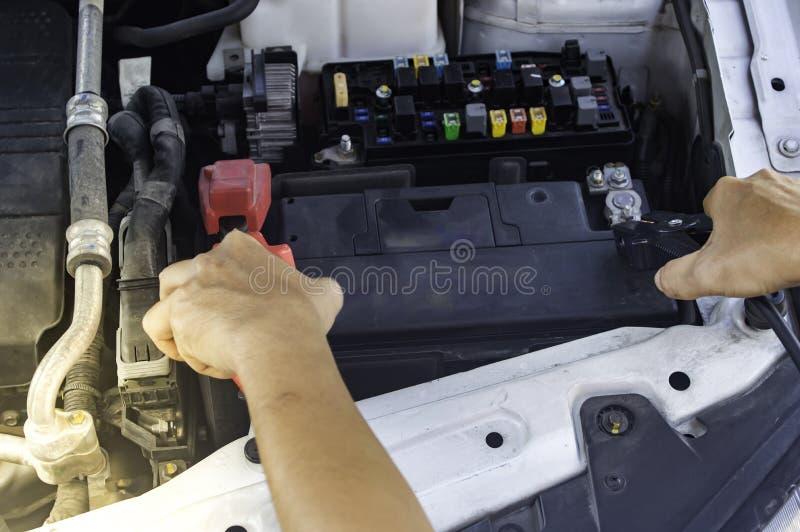 Den auto mekanikern använder ett laddande batteri med elektricitetshoju royaltyfri bild