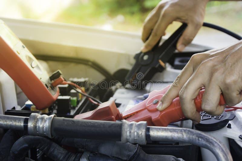 Den auto mekanikern använder ett laddande batteri med elektricitetshoju royaltyfri foto