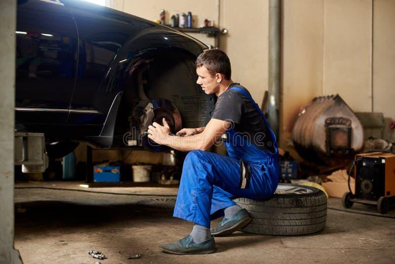 Den auto mekanikern i likformig för smutsigt arbete reparerar framhjulbilen arkivfoto