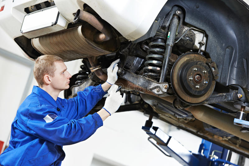 Den Auto mekanikern på bilupphängning reparerar arbete