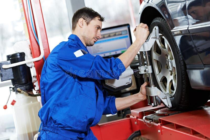 Den Auto mekanikern på rullar justeringsarbete med skruvnyckeln royaltyfri fotografi