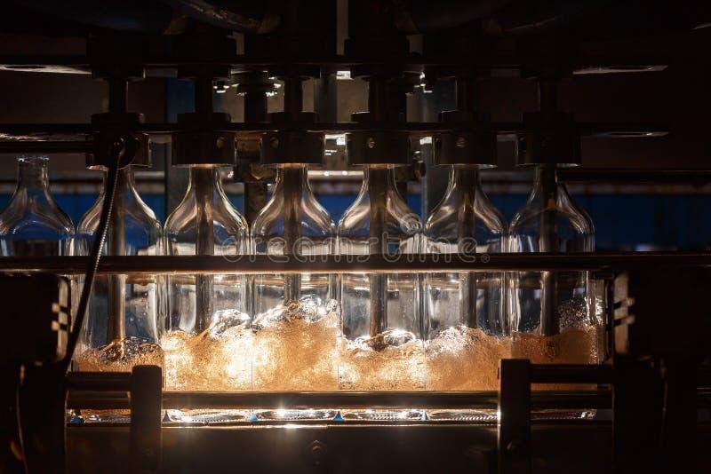 Den automatiska fyllnads- maskinen häller flytande in i glasflaskor Brygga produktion industriell bakgrund arkivfoton