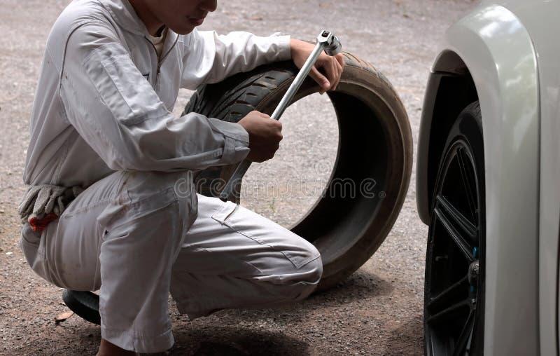Den automatiska mekanikermannen i likformig med gummihjulet och skiftnyckeln för att fixa bilen på reparationen parkera bilen i g royaltyfri fotografi