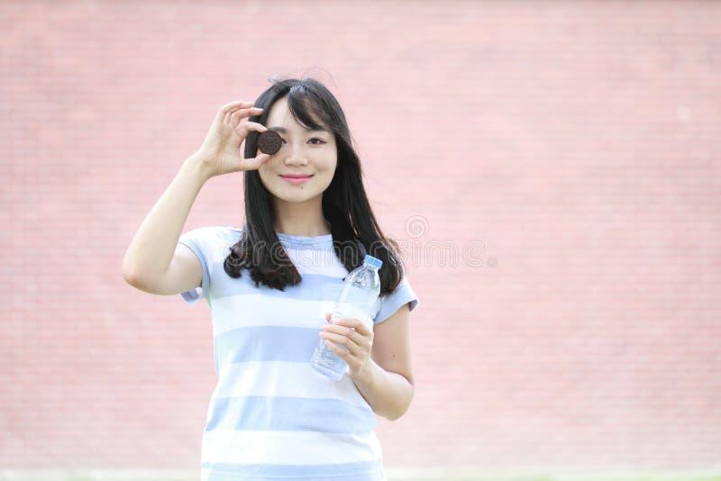Den avkopplade asiatiska kinesiska flickan tycker om fri tid, äter royaltyfri fotografi