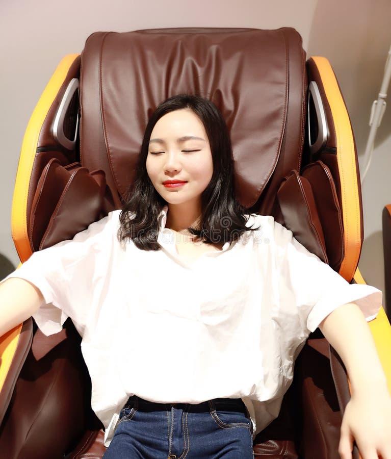 Den avkopplade kvinnaflickan som ligger på elektrisk automatisk massagestol, tycker om hennes fria bekväma tid royaltyfria bilder