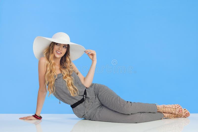 Den avkopplade unga kvinnan i jumpsuit- och solhatt sitter på golv och ser bort royaltyfria bilder