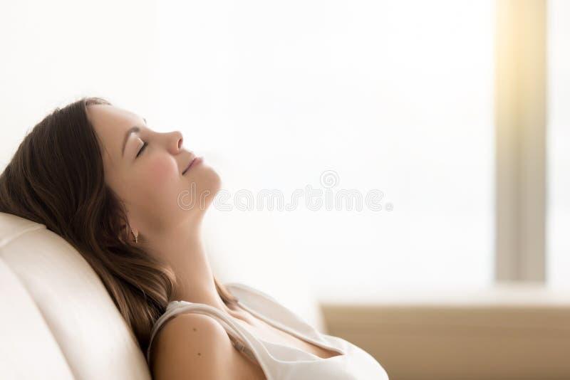 Den avkopplade unga kvinnan som tycker om, vilar på den bekväma soffan, kopieringsspac fotografering för bildbyråer