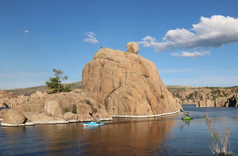 Den avlägsna kayakeren på blå en slät bergsjö som omges men, vaggar royaltyfri foto