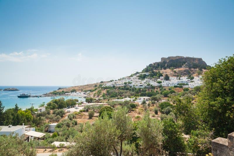 Den avlägsna sikten på den Lindos staden och slotten med forntida fördärvar av akropolen på solig varm dag Ö av Rhodes, Grekland  royaltyfria foton