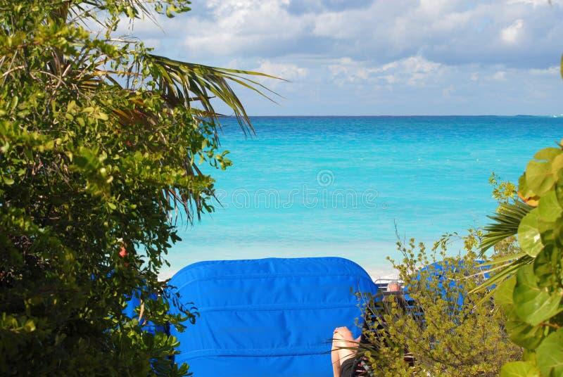 Den avslappnande sikten av sand, vatten och himmel mycket av moln från stranden av en karibisk ö arkivfoton