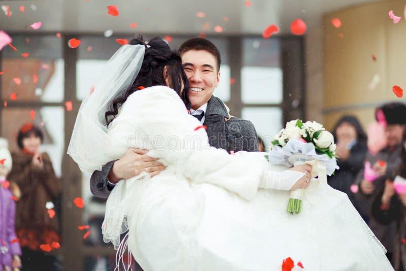 Den bärande bruden för brudgummen i hans armar, folkmassan kastar kronblad och ris lyckligt bröllop arkivbild