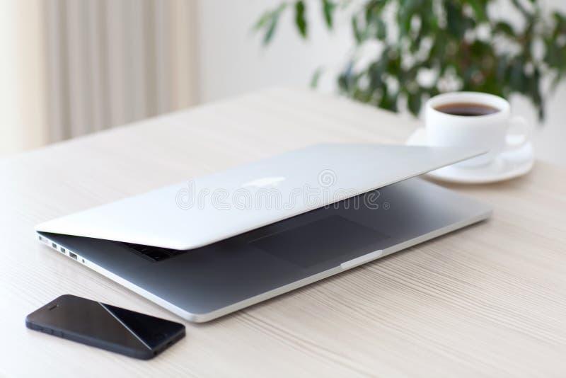 Den bärbar datorMacBook Pro näthinnan och iPhonen 5s ligger på tabellen I fotografering för bildbyråer