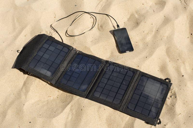Den bärbara solpanelen är på strandladdningsmobiltelefonen arkivfoton