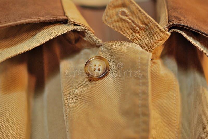 Den bästa knappen på en stilfull regnrock royaltyfri fotografi
