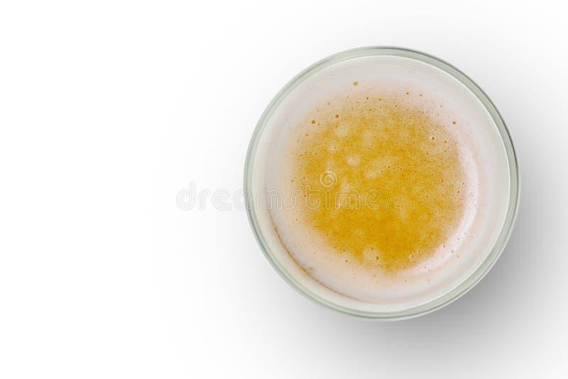 Den bästa sikten av öl bubblar i den glass koppen på vit bakgrund royaltyfri bild