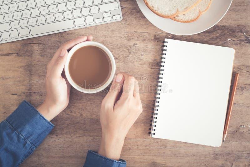Den bästa sikten av affärshandskrivbordet har på kaffe, rostat bröd, anteckningsbokmellanrumet och blyertspennan royaltyfri fotografi