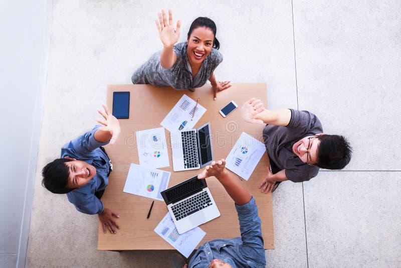 Den bästa sikten av affärsmän och affärskvinnan firar över tabellen i ett möte med kopieringsutrymme på det mobila kontoret Teamw arkivbild