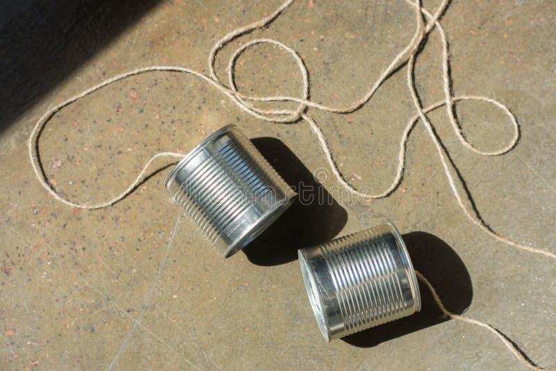 Den bästa sikten av aluminium tenn- cans förband med repet på jordningen arkivbild