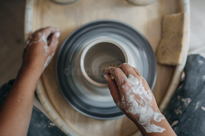 Den bästa sikten av arbeten för keramikerkvinnahänder på krukmakerihjulet, keramiker gör ny keramisk produktion royaltyfria bilder