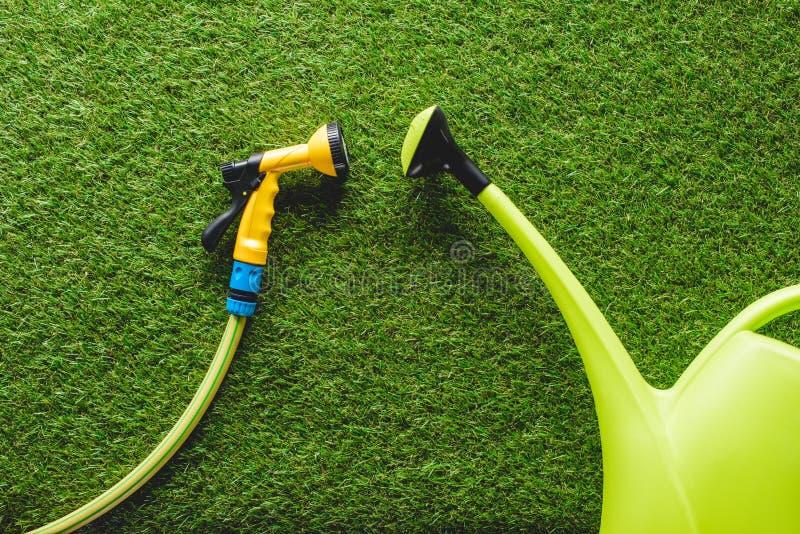 den bästa sikten av att bevattna kan och hosepipen på gräs, minimalistic befruktning arkivbilder