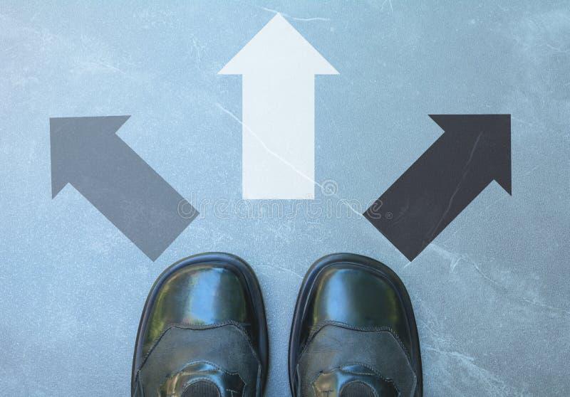 Den bästa sikten av bärande svart för mannen skor att välja en markerad väg arkivbild