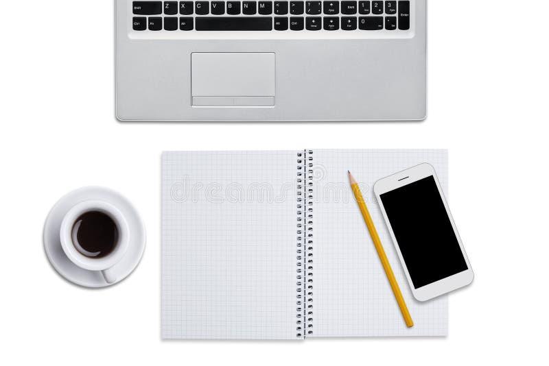 Den bästa sikten av bärbara datorn, spiralanteckningsbok med blyertspennan, ilar telefonen och koppen kaffe som isoleras över vit arkivfoton