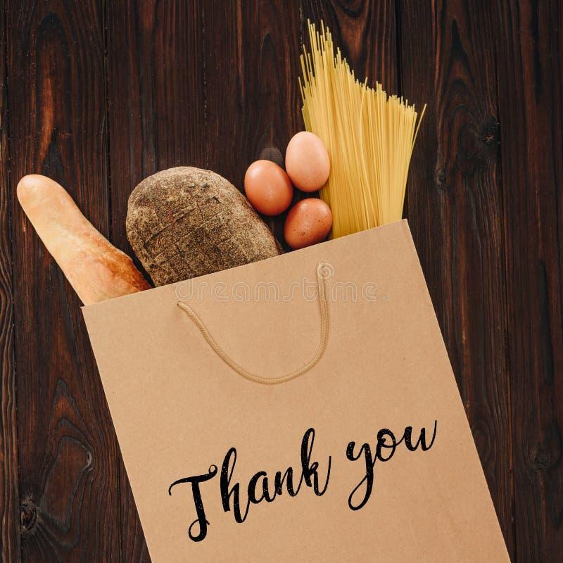 Den bästa sikten av bröd, pasta och ägg i pappers- påse med ord tackar dig royaltyfria bilder