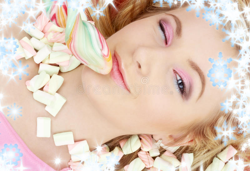 Den bästa sikten av den härliga unga kvinnan med godisar täckte henne ögon som rymmer en klubba, medan ligga på godisar arkivbilder