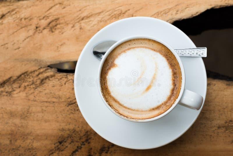 Den bästa sikten av den varma kaffecappuccinokoppen med mjölkar skum på den wood fliken arkivbilder
