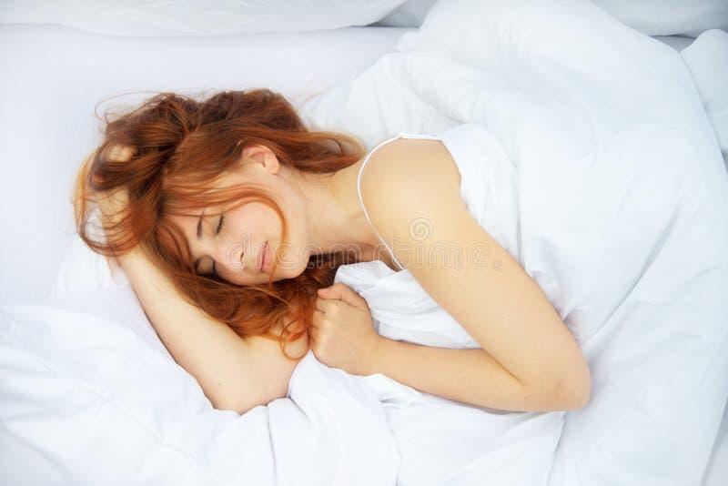 Den bästa sikten av en attraktiv, ung sexig rödhårig kvinna som fläktar hår runt om framsidan, sover, tycker om den nya mjuka sän royaltyfri bild
