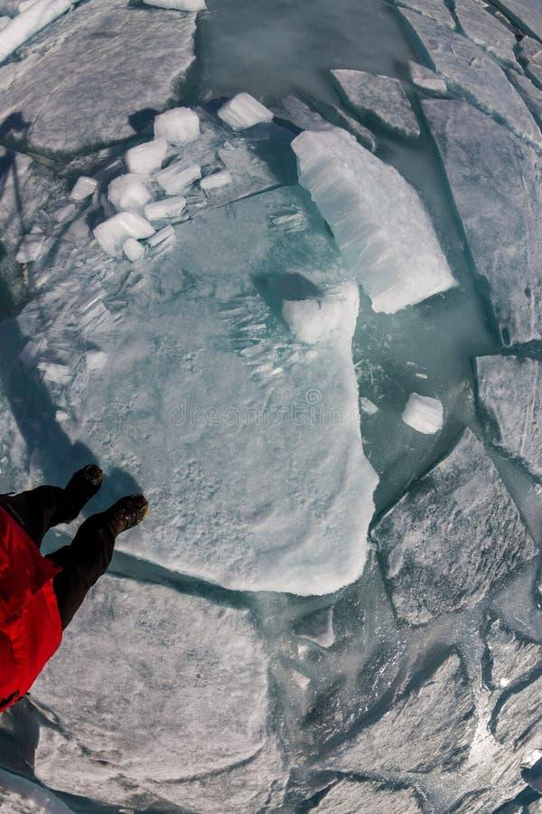 Den bästa sikten av en mänsklig fot på isen täckas med sprickor och H arkivbild