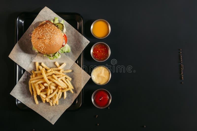 den bästa sikten av fransmannen steker med den läckra hamburgaren på magasinet och blandade såser fotografering för bildbyråer