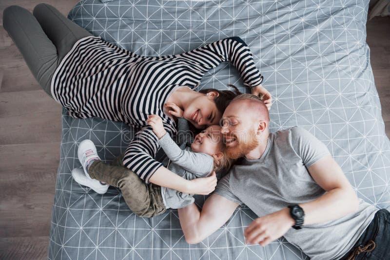 Den bästa sikten av härligt barn fostrar, fadern och deras dotter som ser kameran och ler, medan ligga på sänghuvudet till royaltyfri foto