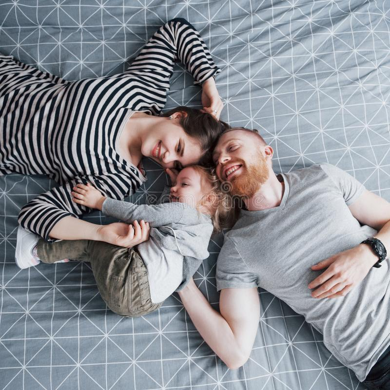 Den bästa sikten av härligt barn fostrar, fadern och deras dotter som ser kameran och ler, medan ligga på sänghuvudet till arkivfoto