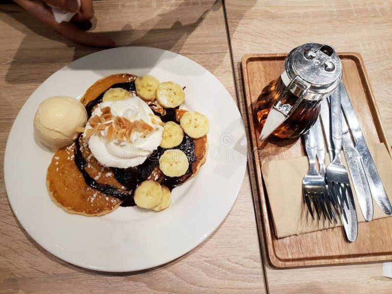 Den bästa sikten av honungrostat bröd med glass, vanilj, banan skivade, piskar kräm och och honung på den vita plattan royaltyfria foton
