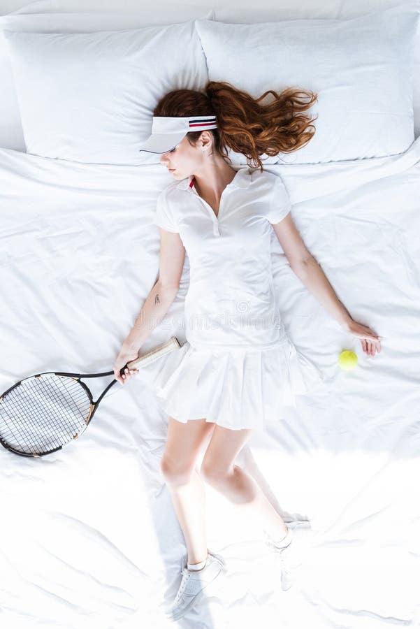 Den bästa sikten av kvinnan i tennis beklär att sova på säng med racket arkivfoton