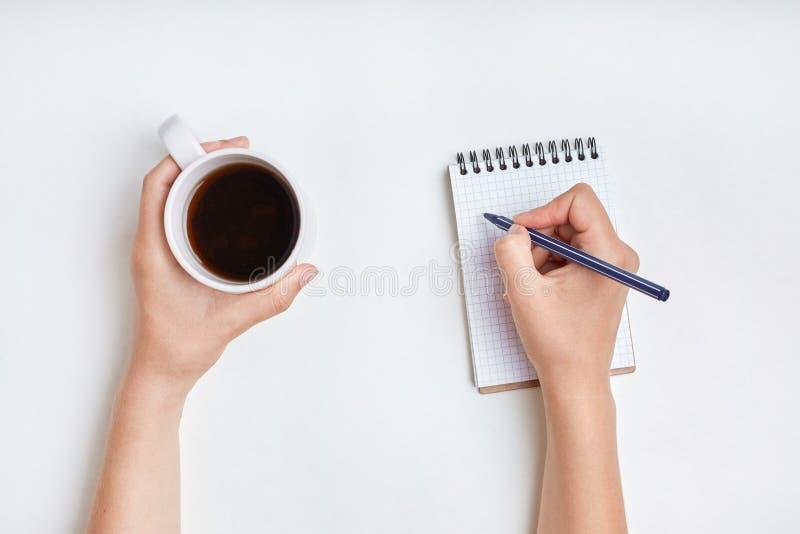 Den bästa sikten av den kvinnliga handen skriver i spiralanteckningsbok, tar anmärkningar w arkivfoto