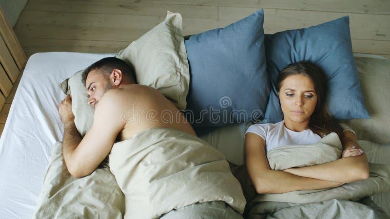 Den bästa sikten av liggande sömnlösa par för rubbningen i säng som kränks på grund av, grälar royaltyfria bilder