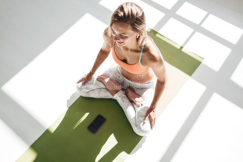 Den bästa sikten av lotusblomma för yoga för övning för vuxen människapassformkvinnan poserar på matt kondition, genom att använd arkivbilder