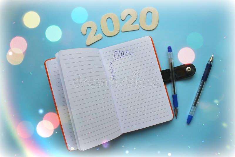Den bästa sikten av 2020 mål listar med notepaden på blå bakgrund royaltyfri fotografi
