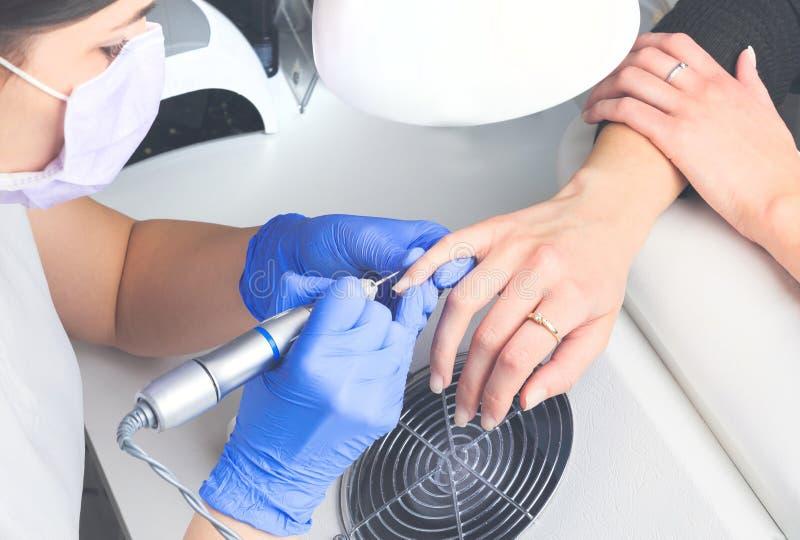 Den bästa sikten av manikyristen i blåa rubber handskar och det medicinska maskeringsrengöringnagelbandet på kvinnlig spikar geno fotografering för bildbyråer