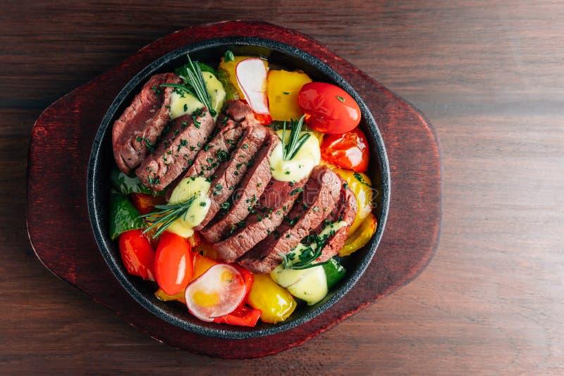 Den bästa sikten av medelsällsynt nötköttbiff tjänade som i varm platta med tomaten, spansk peppar, rädisan och rosmarin royaltyfri foto